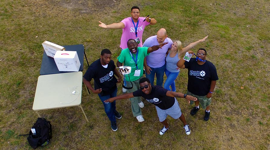 A group posing for the drone photo from up above them. The Newark International Film Festival's Drone Workshop with Raymond Spencer.